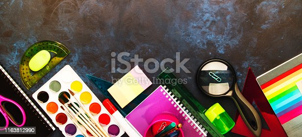 istock Back to school background with space for text, notebooks, pens, pencils, other stationery on blue chalk board desk, education concept, flat lay, top view 1163812990