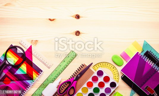 istock Back to school background with space for text, notebooks, pens, pencils, other stationery on light wooden school desk, education concept, flat lay, top view 1163813016