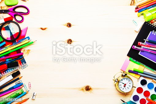 istock Back to school background with space for text, notebooks, pens, pencils, other stationery on light wooden school desk, education concept, flat lay, top view 1163813046