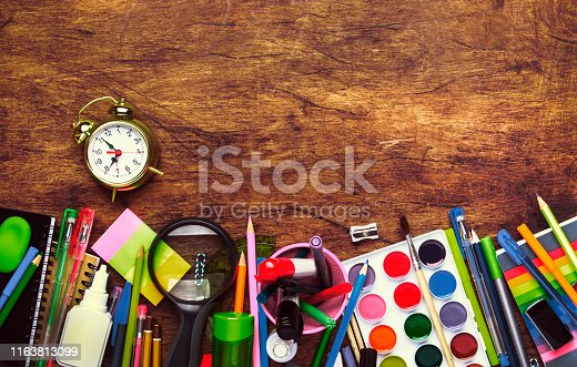 istock Back to school background with space for text, notebooks, pens, pencils, other stationery on wooden school desk, education concept, flat lay, top view 1163813099
