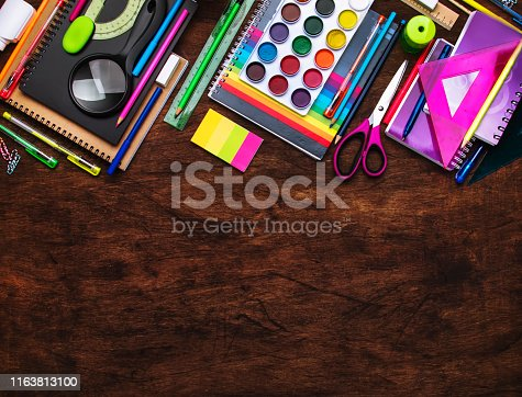 istock Back to school background with space for text, notebooks, pens, pencils, other stationery on wooden school desk, education concept, flat lay, top view 1163813100