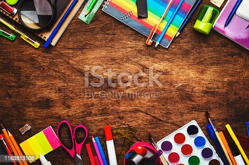 istock Back to school background with space for text, notebooks, pens, pencils, other stationery on wooden school desk, education concept, flat lay, top view 1163813105