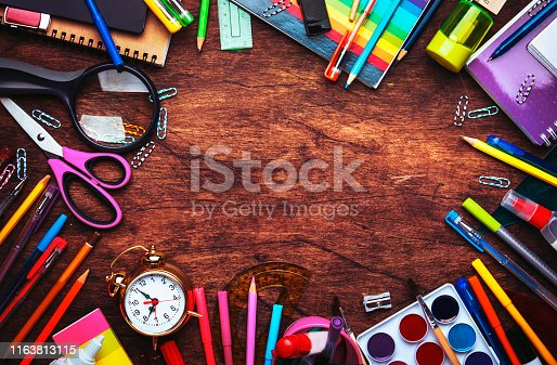 istock Back to school background with space for text, notebooks, pens, pencils, other stationery on wooden school desk, education concept, flat lay, top view 1163813115