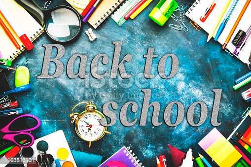 istock Back to school background with space for text, notebooks, pens, pencils, other stationery on wooden school desk, education concept, flat lay, top view 1163813131