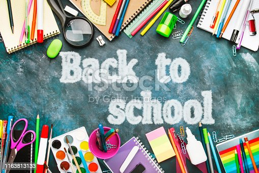 istock Back to school background with text chalk imitation, notebooks, pens, pencils, other stationery on blue chalk board desk, education concept, flat lay, top view 1163813133