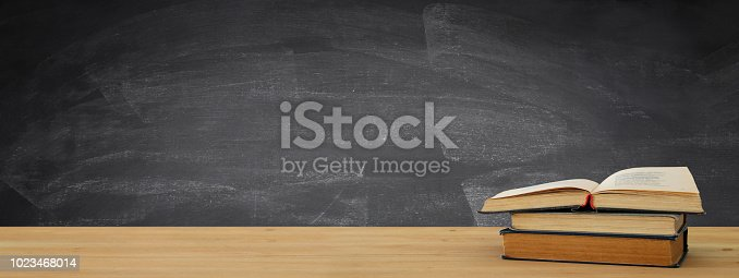 istock back to school banner. stack of books over wooden desk in front of blackboard. 1023468014