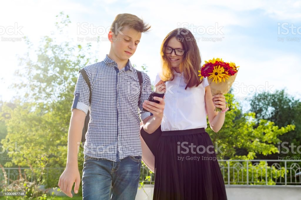 Back to school, Children teenagers go first day to school, with bouquet of flowers, smile, talk. stock photo