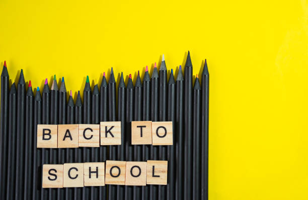 back to school collected from wooden elements letter block on bunch of colourful blacked pencils on yellow background stock photo