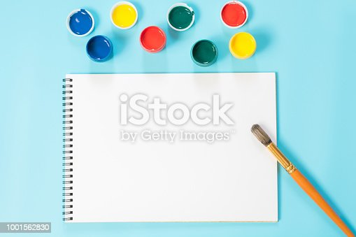 istock Back to school. Colorful paints, album and brush on punchy blue. Copy space. Top view. 1001562830