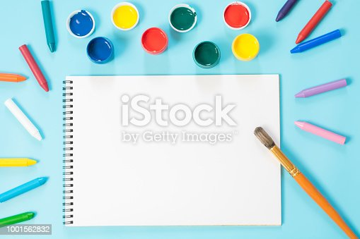 istock Back to school. Colorful paints, album and brush on punchy blue. Copy space. Top view. 1001562832
