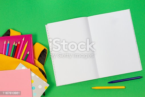 istock Back to school concept. Backpack with school supplies and open paper notebook on green background. Top view 1167610931