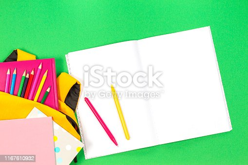 istock Back to school concept. Backpack with school supplies and open paper notebook on green background. Top view 1167610932