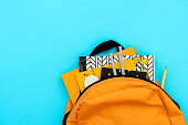 Back to school concept. Backpack with school supplies on blue background. Top view. Copy space. Flat lay