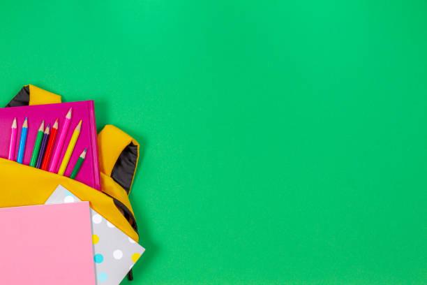 Zurück zum Schulkonzept. Rucksack mit Schulmaterial auf hellgrünem Hintergrund. Ansicht von oben – Foto