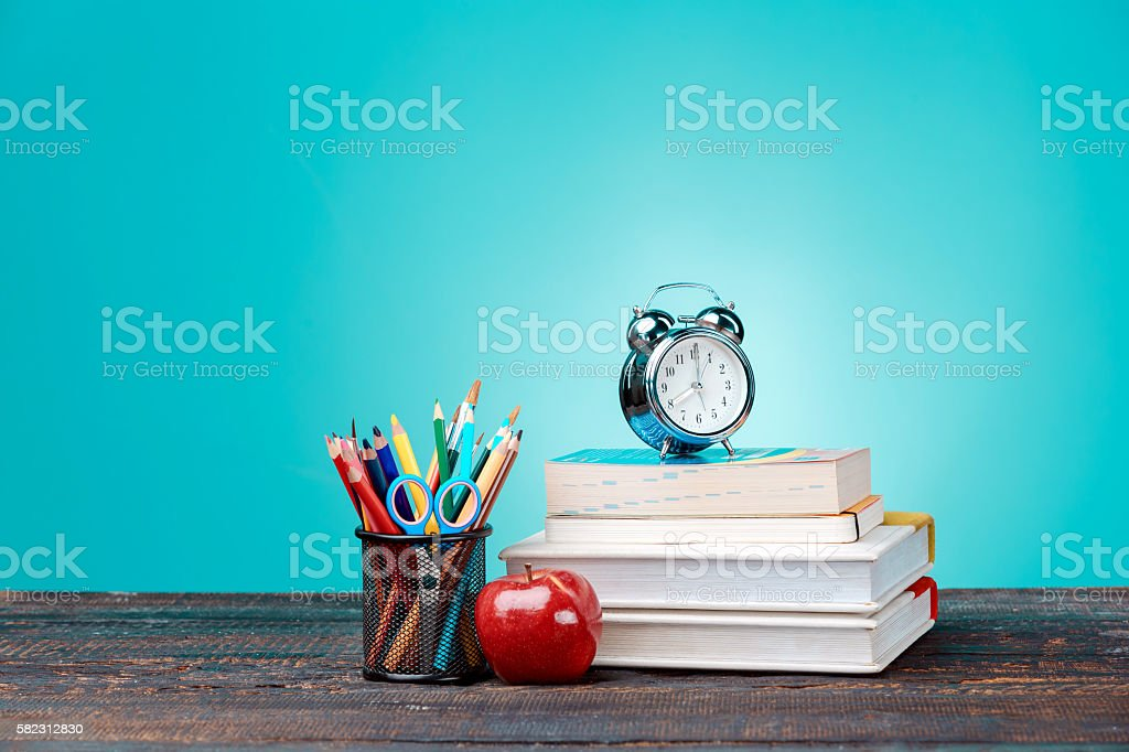 Back to School concept. Books, colored pencils and clock stock photo