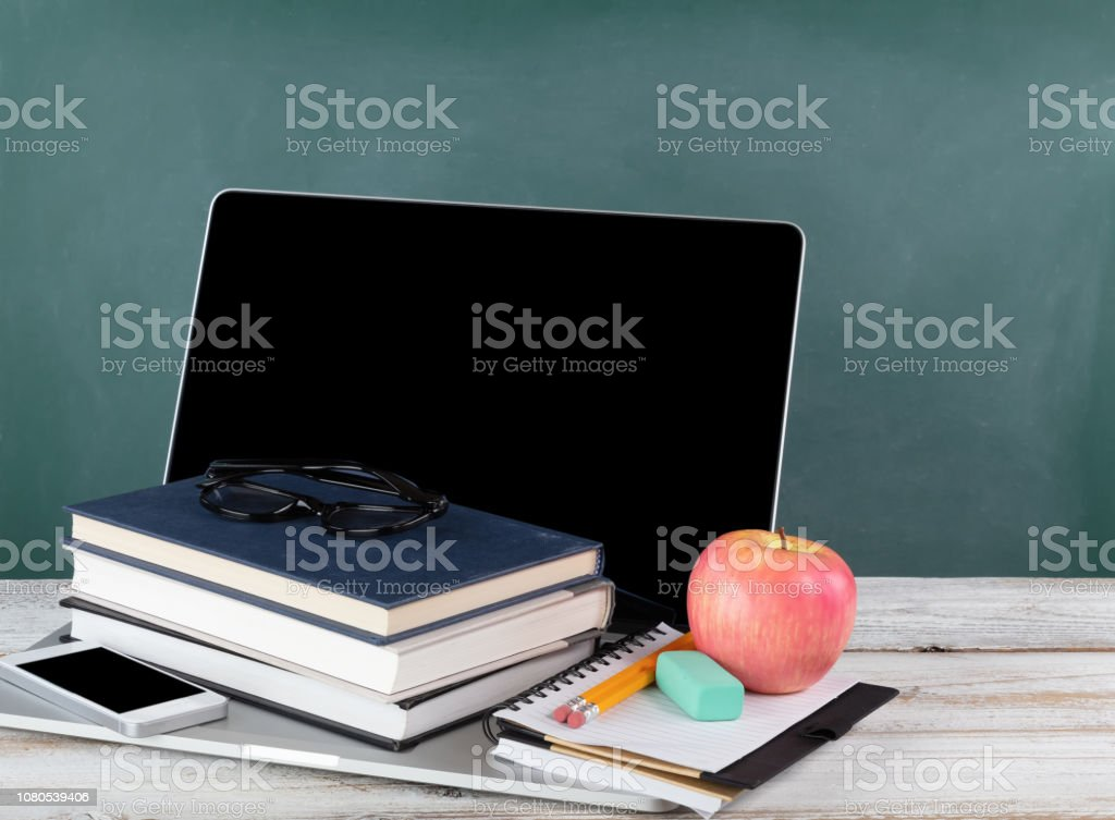 Back to school concept consisting of technology and traditional stationery with green chalkboard stock photo