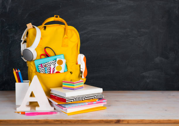 Back to school concept. Educational supplies on table before blackboard stock photo