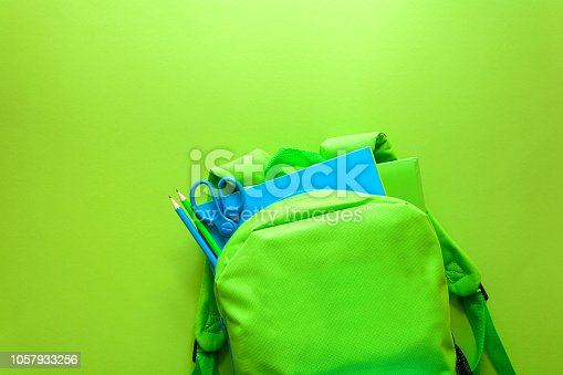 Back to school concept. Green backpack with school supplies on green background. Top view. Copy space
