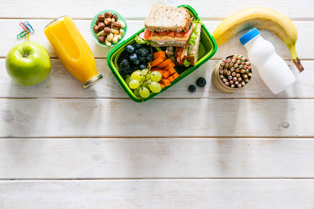 Back to school concept - lunch box with juice, apple and banana