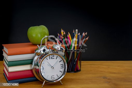 istock back to school concept. stack of books and pencils over wooden desk in front of blackboard 1023074060