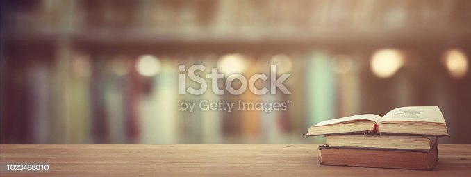 istock back to school concept. stack of books over wooden desk in front of library. 1023468010