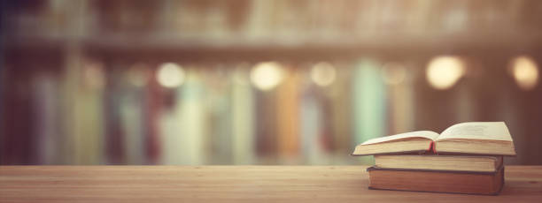 back to school concept. stack of books over wooden desk in front of library. – zdjęcie