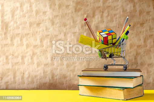 istock Back to school concept. Stack of books with school supplies in shopping cart 1148663964