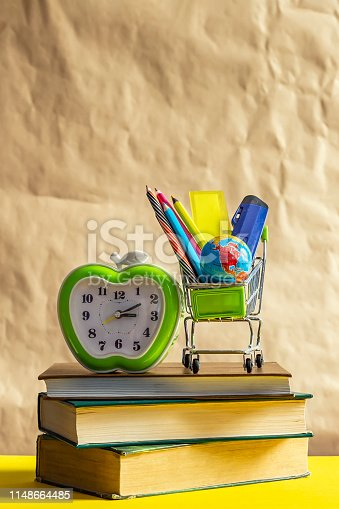 istock Back to school concept. Stack of books with school supplies in shopping cart 1148664485