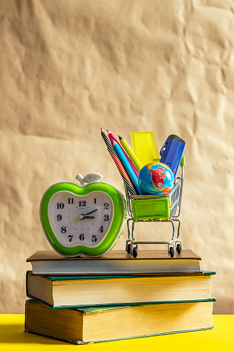 1045293630 istock photo Back to school concept. Stack of books with school supplies in shopping cart 1148664485