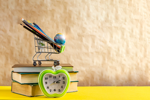 1045293630 istock photo Back to school concept. Stack of books with school supplies in shopping cart 1150105255