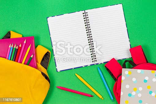 istock Back to school concept. Two backpacks with school supplies, books and notebooks and open notebook on light green background. Top view 1167610801
