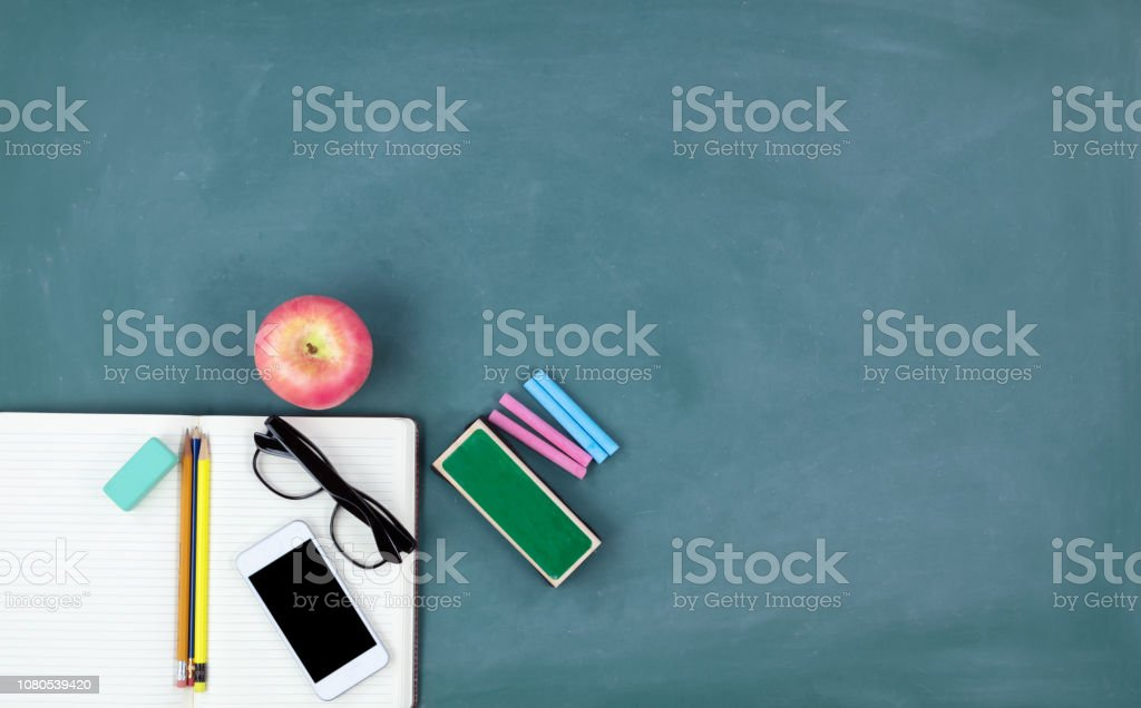 Back to school concept with basic stationery on a green chalkboard background stock photo