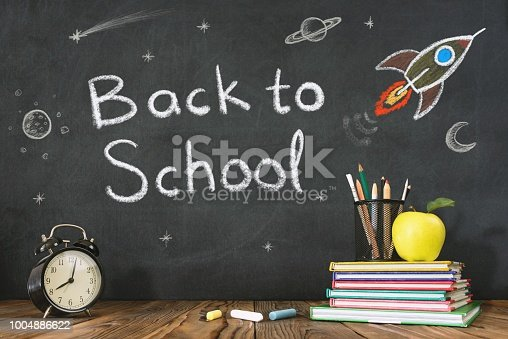 istock Back to School Concept with Hand Drawn Rocket on Blackboard 1004886622