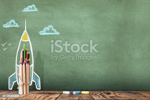 istock Back to School Concept with Hand Drawn Rocket on Blackboard 972836068