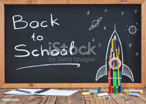 istock Back to School Concept with Hand Drawn Rocket on Blackboard 988640934