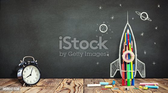 istock Back to School Concept with Hand Drawn Rocket on Blackboard 988641536