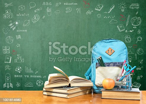 istock Back to school concept with school books, textbooks, backpack and stationery supplies on classroom desk with teacher's green chalkboard background with educational doodle for new academic year begin 1001814580