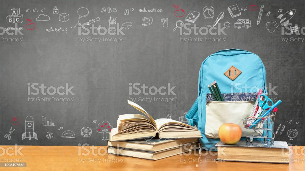 Back to school concept with school books, textbooks, backpack and stationery supplies on classroom desk with teacher's black chalkboard background with educational doodle for new academic year begin royalty-free stock photo