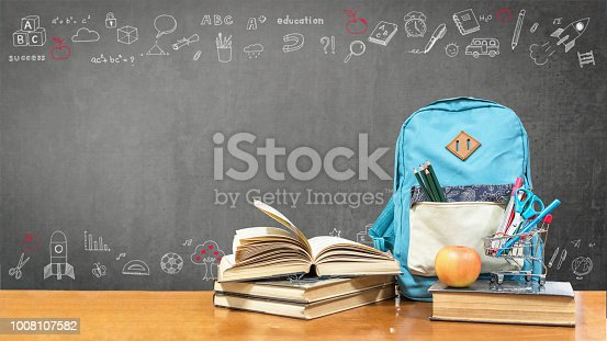 istock Back to school concept with school books, textbooks, backpack and stationery supplies on classroom desk with teacher's black chalkboard background with educational doodle for new academic year begin 1008107582