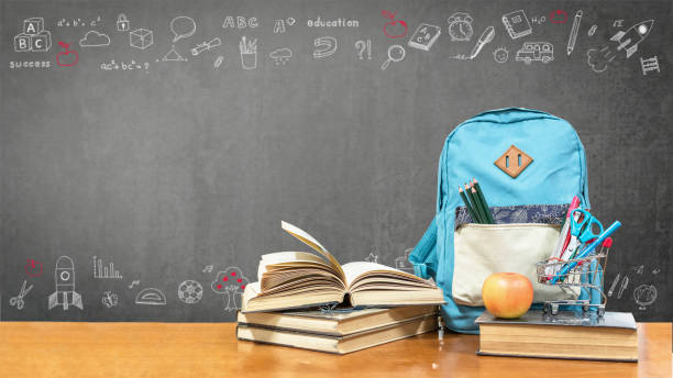 Back to school concept with school books, textbooks, backpack and stationery supplies on classroom desk with teacher's black chalkboard background with educational doodle for new academic year begin Back to school concept with school books, textbooks, backpack and stationery supplies on classroom desk with teacher's black chalkboard background with educational doodle for new academic year begin aboard stock pictures, royalty-free photos & images