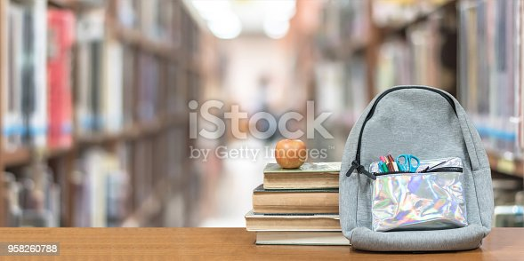 istock Back to school concept with school books, textbooks, backpack and stationery supplies on classroom desk with library or class background for educational new academic year begin or study term start 958260788