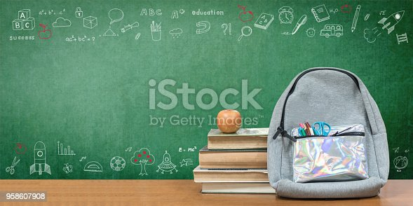 istock Back to school concept with school books, textbooks, backpack and stationery supplies on classroom desk with teacher's chalkboard background with educational doodle for new academic year begin 958607908