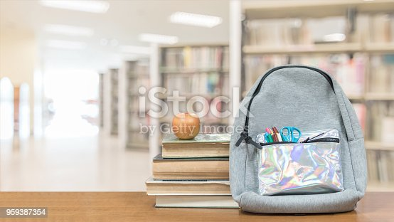 istock Back to school concept with school books, textbooks, backpack and stationery supplies on classroom desk with library or class background for educational new academic year begin or study term start 959387354