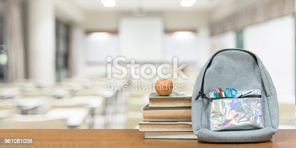 istock Back to school concept with school books, textbooks, backpack and stationery supplies on classroom desk with library or class background for educational new academic year begin or study term start 961081038