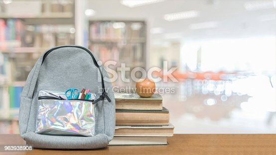 istock Back to school concept with school books, textbooks, backpack and stationery supplies on classroom desk with library or class background for educational new academic year begin or study term start 963938908