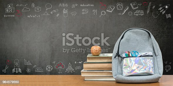 istock Back to school concept with school books, textbooks, backpack and stationery supplies on classroom desk with teacher's chalkboard background with educational doodle for new academic year begin 964579550