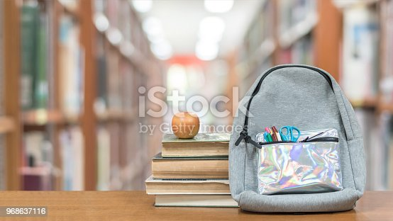 istock Back to school concept with school books, textbooks, backpack and stationery supplies on classroom desk with library or class background for educational new academic year begin or study term start 968637116