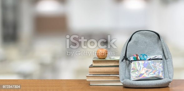 istock Back to school concept with school books, textbooks, backpack and stationery supplies on classroom desk with library or class background for educational new academic year begin or study term start 972347304