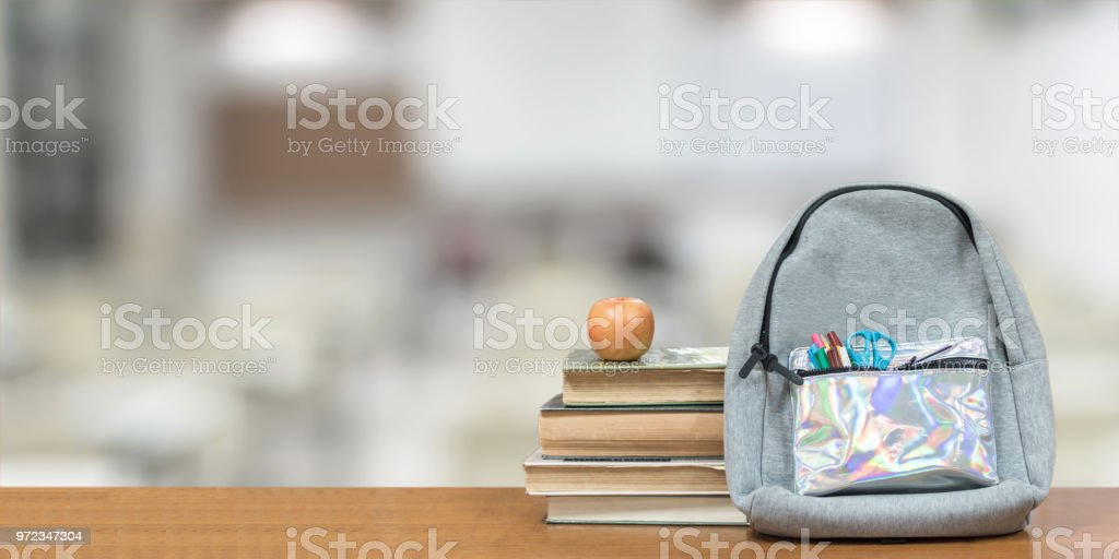 Back to school concept with school books, textbooks, backpack and stationery supplies on classroom desk with library or class background for educational new academic year begin or study term start stock photo