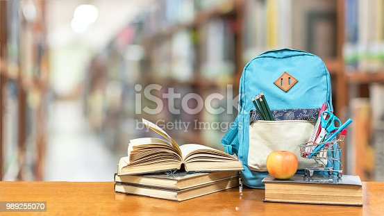 istock Back to school concept with school books, textbooks, backpack and stationery supplies on classroom desk with library or class background for educational new academic year begin or study term start 989255070